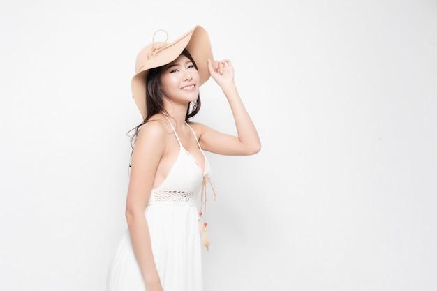 La donna sta sorridendo felicità indossando un abito estivo bianco e cappello da sole è in piedi isolato su bianco