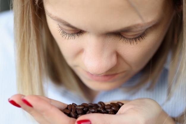 La donna sta annusando i chicchi di caffè sul suo palmo. come distinguere il vero caffè dal falso concetto