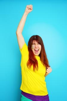 La donna è tifosa di calcio in maglietta gialla su sfondo blu