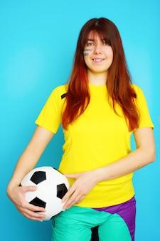 La donna è tifosa di calcio in maglietta gialla con pallone da calcio su sfondo blu