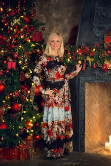 La donna è in piedi accanto al caminetto contro l'albero di natale