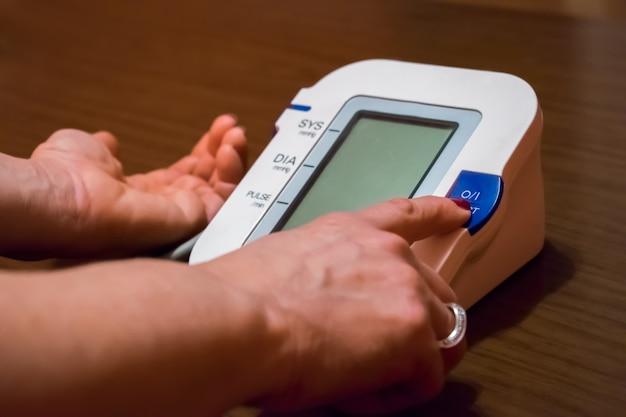 La donna sta prendendo cura della salute con il monitor del battito del focolaio e la pressione sanguigna
