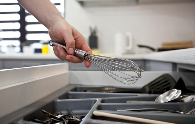 La donna sta prendendo l'attrezzatura da cucina dallo scaffale con stoviglie
