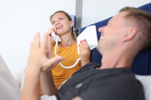La donna sta parlando al telefono mentre si trova con l'uomo sul letto nel concetto di servizio dell'hotel della camera d'albergo