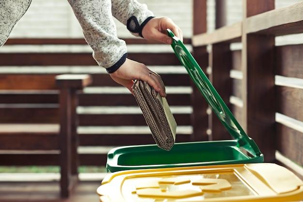 La donna getta il cartone in uno dei tre bidoni della spazzatura