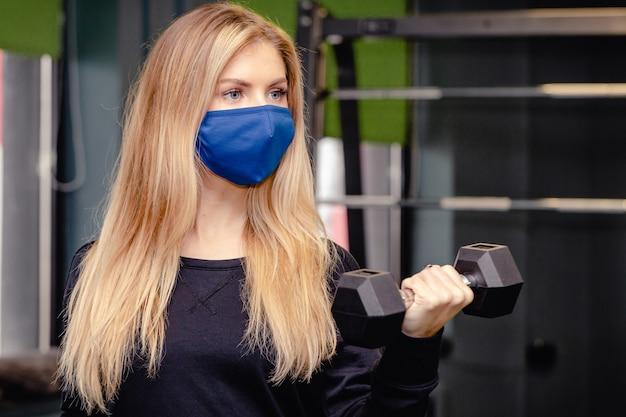 La donna si sta allenando in palestra durante la pandemia.