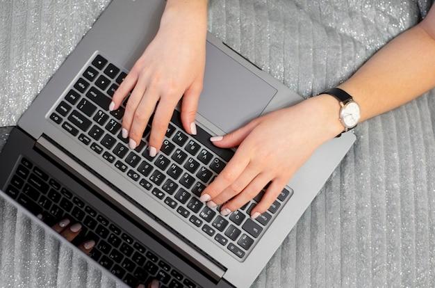 La donna sta scrivendo sulla tastiera vista dall'alto