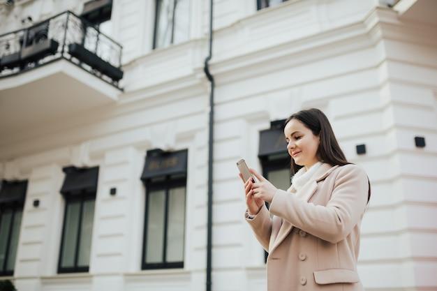 Donna sta usando il telefono mentre era in piedi per strada nel centro della città