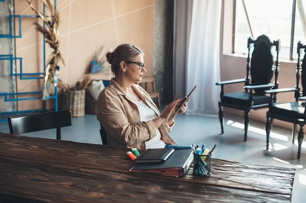 Donna sta usando una tavoletta a casa dopo aver lavorato