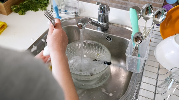 La donna sta lavando le forchette delle posate con le mani insaponando la spugna con detergenti in cucina a casa nel lavandino di metallo, vista dal retro