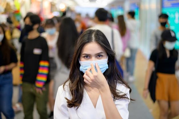 Una donna indossa una maschera protettiva per strada con persone affollate durante la pandemia covid-19, protezione dal coronavirus, concetto di stili di vita di sicurezza