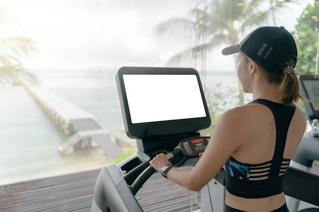 La donna sta lavorando in palestra. facendo allenamento cardio sul tapis roulant con mockup di schermo bianco, grandi finestre con vista sull'oceano che piove fuori.