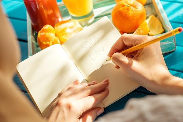La donna sta scrivendo sul suo taccuino nella mattina soleggiata.