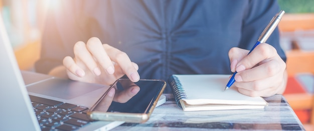 La donna sta scrivendo su un taccuino con una penna e sta usando un telefono cellulare nell'ufficio. striscione web.