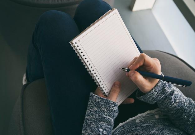 La donna sta scrivendo sul quaderno di carta