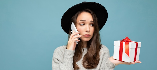 Donna isolata su sfondo blu muro che indossa un cappello nero e maglione grigio azienda confezione regalo parlando al telefono cellulare e guardando al lato.