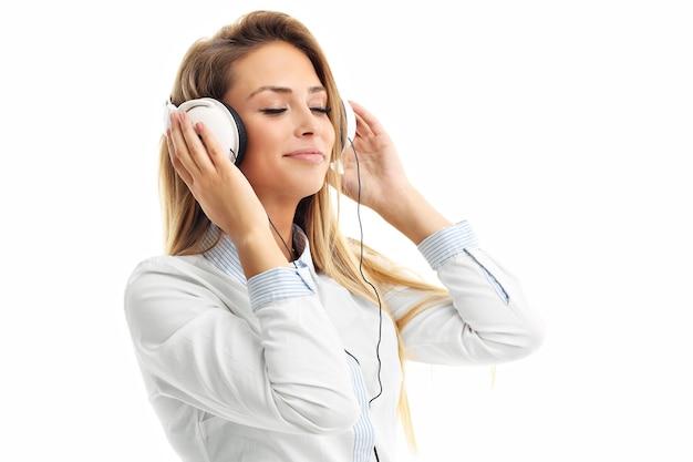 Donna isolata su bianco con le cuffie che ascolta la musica