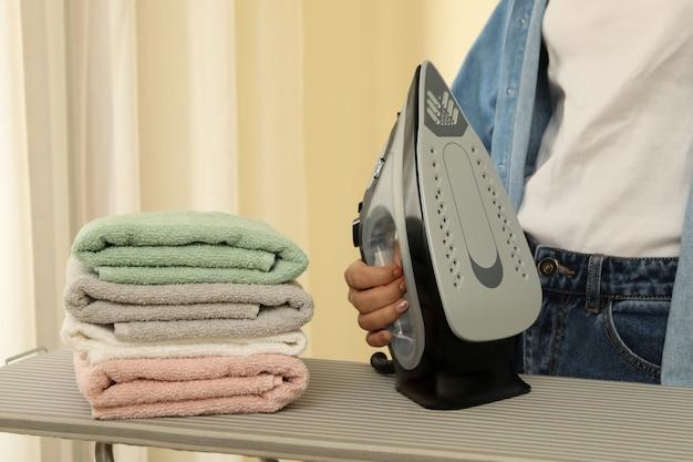 La donna in jeans tiene il ferro sull'asse da stiro con una pila di asciugamani