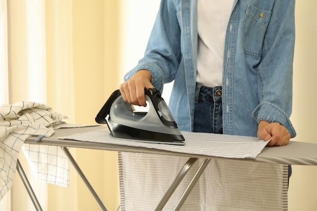Donna in jeans stiratura asciugatutto da cucina sull'asse da stiro