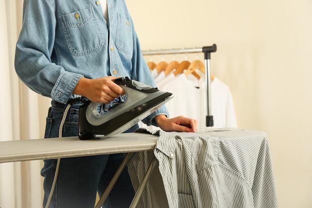 Donna in jeans stirare la camicia con il ferro