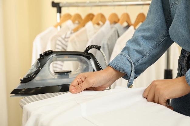 Donna in jeans stirare la maglietta con il ferro