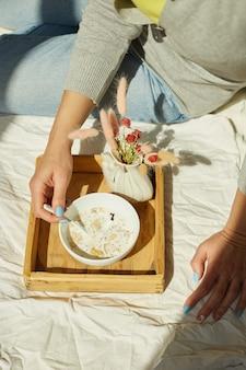 Donna in jeans seduta sul letto e mangiare una sana ciotola di muesli durante la luce del sole del mattino, colazione a letto.