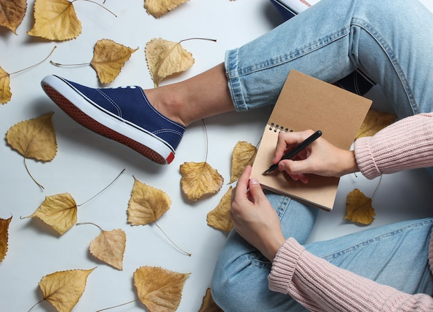 Una donna in jeans e scarpe da ginnastica si siede sul tavolo bianco tra le foglie gialle cadute e scrive su un quaderno. giornalista di lavoro. tempo d'autunno. spazio di lavoro.