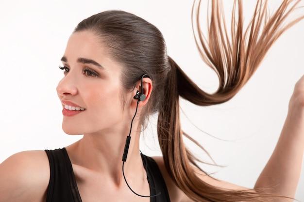 Donna in jogging nero top ascoltando musica sugli auricolari in posa isolato su white