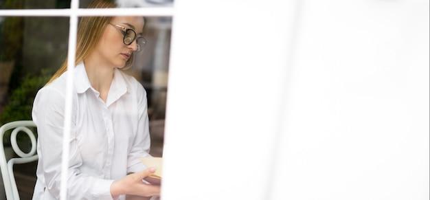Una giornalista donna in un caffè vicino alla finestra guarda gli appunti su un taccuino, pianifica riunioni e una giornata lavorativa. la donna d'affari prende il caffè mattutino nella caffetteria. concetto di stile di vita. bandiera.