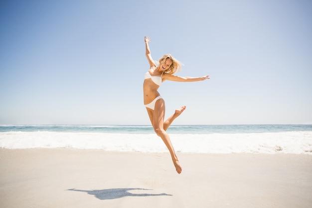 La donna che salta sulla spiaggia