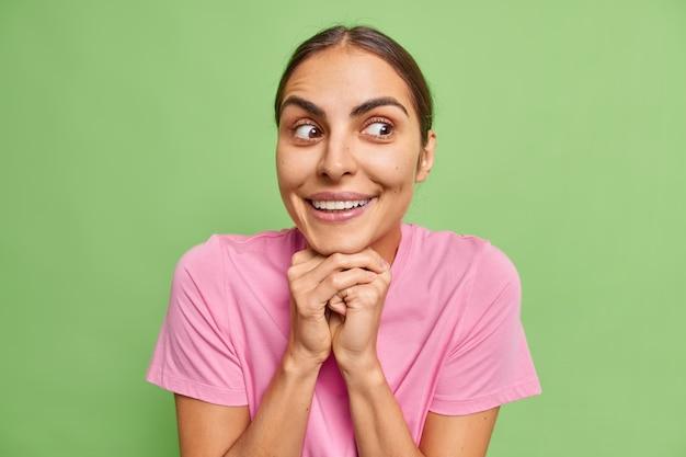 La donna tiene le mani sotto il mento sorride felicemente guarda con espressione curiosa a parte indossa una maglietta rosa casual sul verde nota qualcosa di interessante