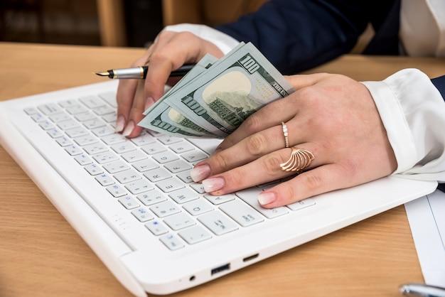 La donna tiene le mani in dollari