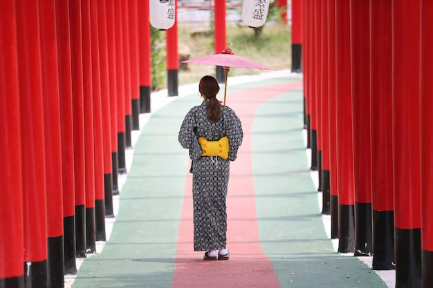 Una donna in kimono con in mano un ombrello che entra nel santuario, nel giardino giapponese.