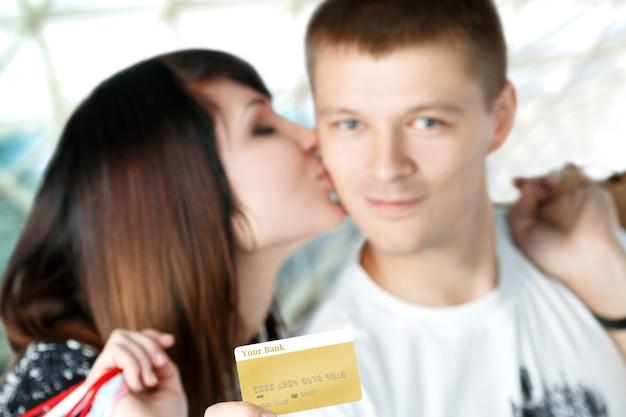 Donna che bacia giovane uomo in possesso di carta di credito concentrarsi sulla carta