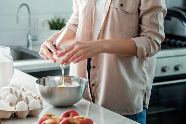 Una donna in cucina rompe un uovo di gallina con una ciotola. cucinando.
