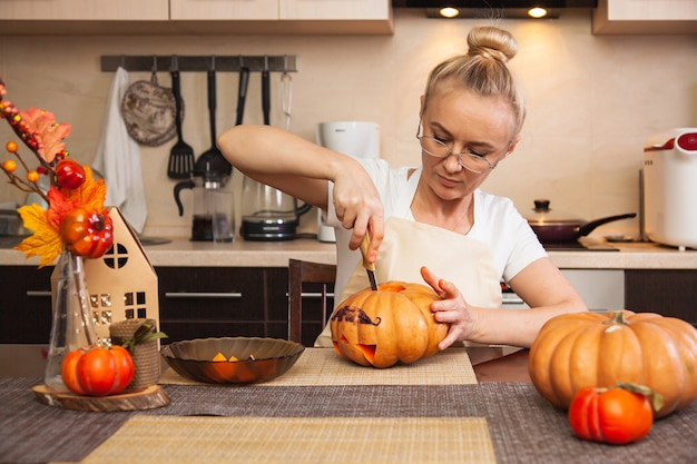 La donna in cucina scolpisce una zucca per halloween in una stanza con decorazioni autunnali e una lampada. casa accogliente e preparazione per halloween.