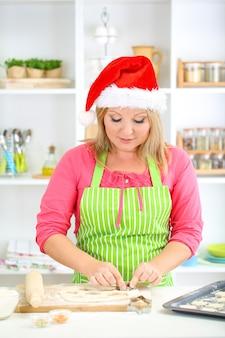 Donna in cucina durante la cottura dei biscotti di natale