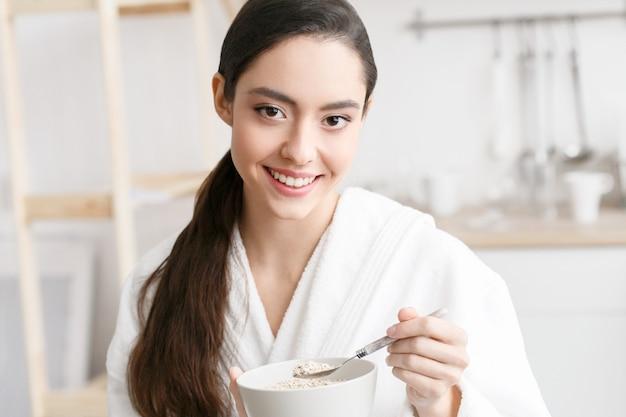 Donna sulla casa della cucina in accappatoio che mangia prima colazione. bellissimo cibo femminile a casa. colpo dello studio.