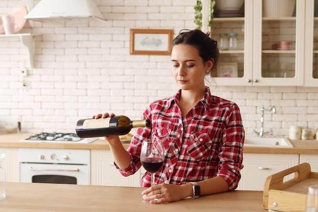 La donna in cucina versa il vino in un bicchiere