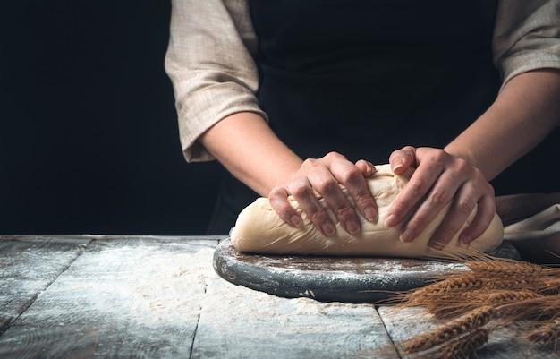 Una donna impasta la pasta su uno sfondo scuro vintage.