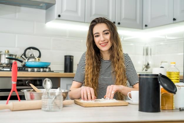 La donna impasta la pasta con un ingrediente diverso