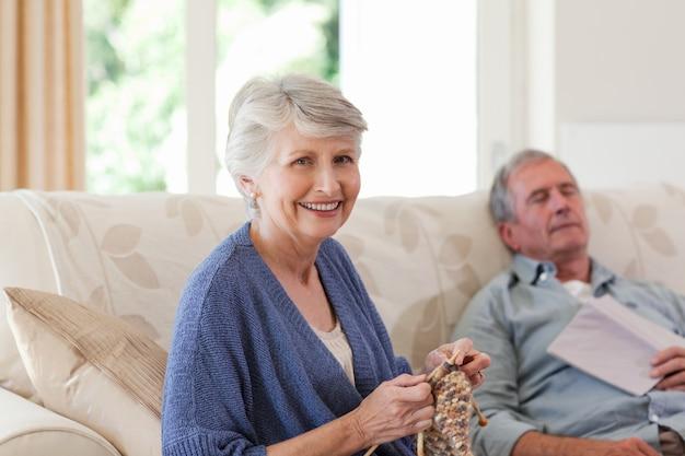 Donna che lavora a maglia mentre suo marito sta dormendo