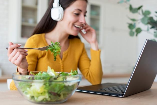Donna al computer portatile che mangia insalata