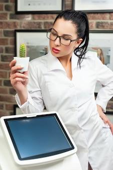 La donna in uno studio di epilazione laser posa con un cactus