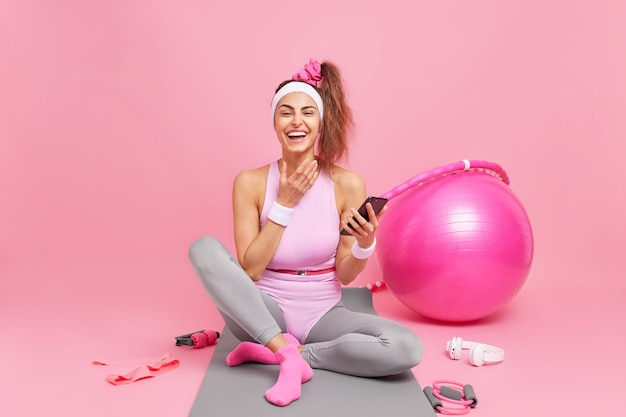 La donna ride con gioia tiene il telefono cellulare si gode l'allenamento fitness vestito in body si siede sul tappetino circondato da pose di hula hoop fitball