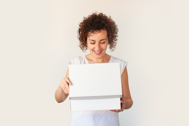 La donna ride durante l'apertura di una scatola su uno sfondo bianco isolato
