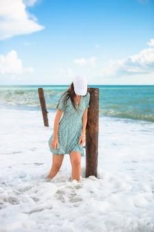 Donna che pone sulla spiaggia godendo le vacanze estive guardando il mare
