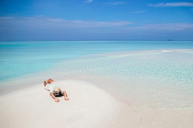 Donna sdraiata sulla spiaggia godendo le vacanze estive guardando il mare the