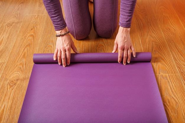 Una donna stende un tappetino da yoga lilla sul pavimento di legno. donne che praticano yoga. uno stile di vita sano in isolamento.