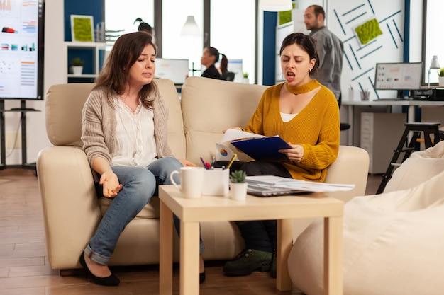 Leader della donna che urla al dipendente seduto sul divano in una nuova attività di avvio, sconvolto da un cattivo accordo contrattuale